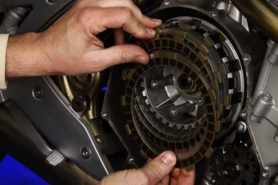 mecanico aguanta con las manos un embrague roto