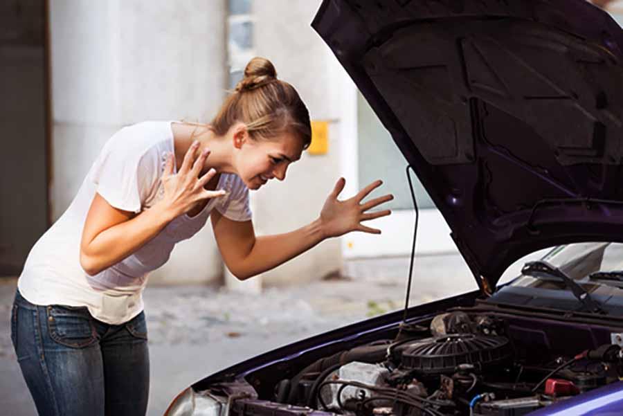 mujer mira el motor del coche averiado