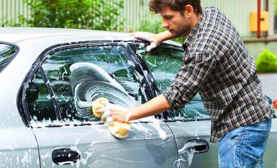 chico limpiando coche plateado con una esponja y jabon