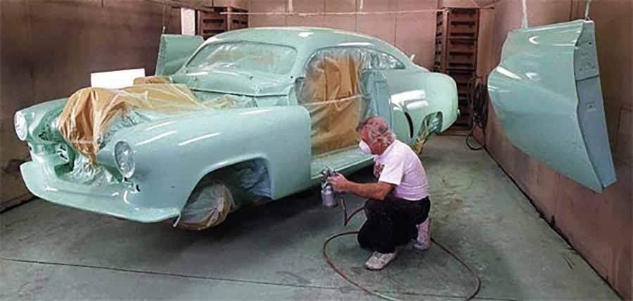 hombre pinta coche antiguo azul