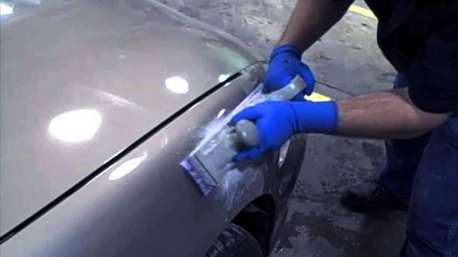 lijar la masilla de relleno de un coche gris