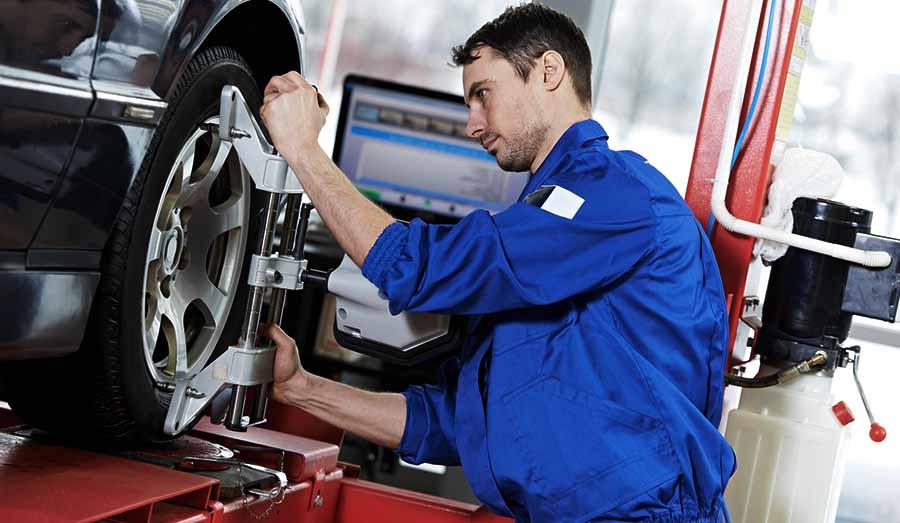 mecanico hace paralelo coche en rueda de coche rojo