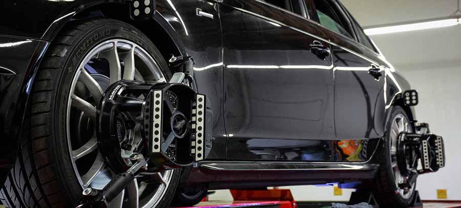Coche negro subido en plataforma con ruedas conectadas a la maquina de hacer el paralelo del coche