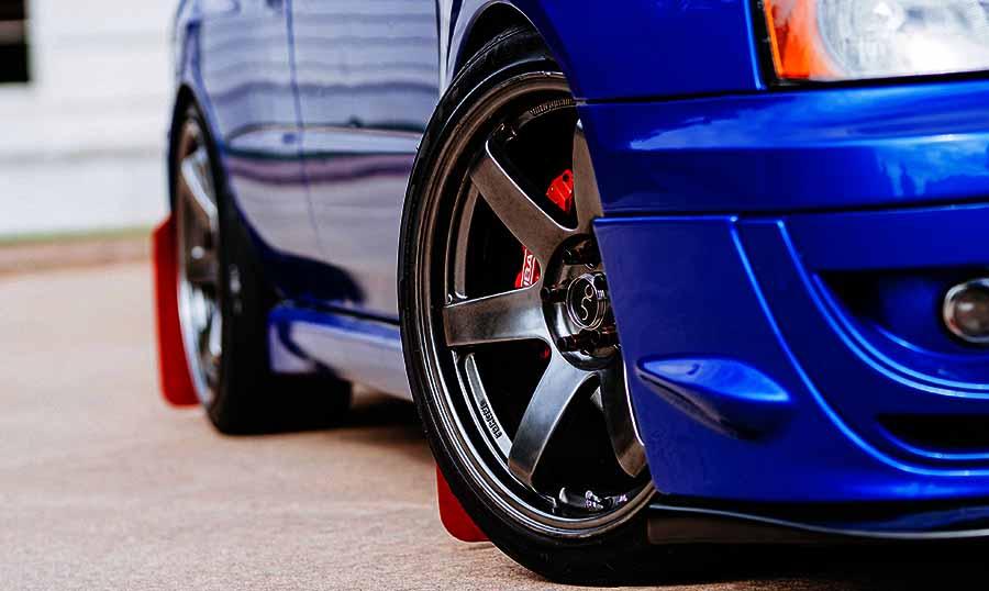 rueda delantera con llantas de un coche azul metalizado