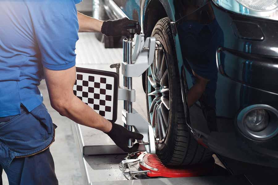 mecanico hace paralelo del coche con una maquina en una rueda