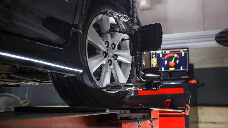 coche en el elevado en un taller con sensores en las ruedas para alineación de las ruedas y verificación de inclinacion