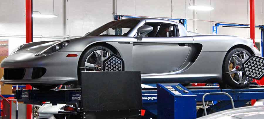 Coche gris elevado en plataforma con ruedas conectadas a la maquina de hacer alineacion de la direccion