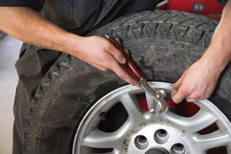 mecanico pone contrapesos en una rueda