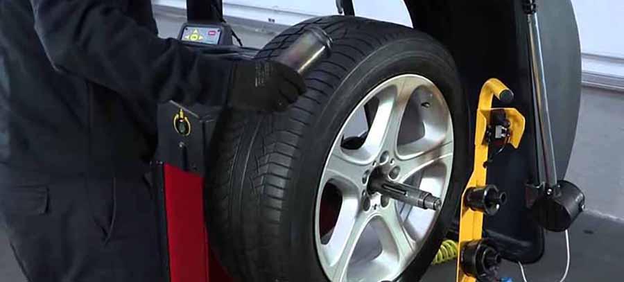 mecanico trabaja con maquina equilibrar ruedas