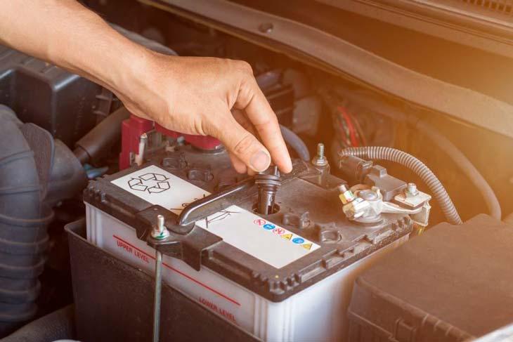 Persona desconectando los bornes de la bateria